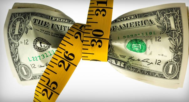 One dollar banknotes tied up with measuring tape against white background